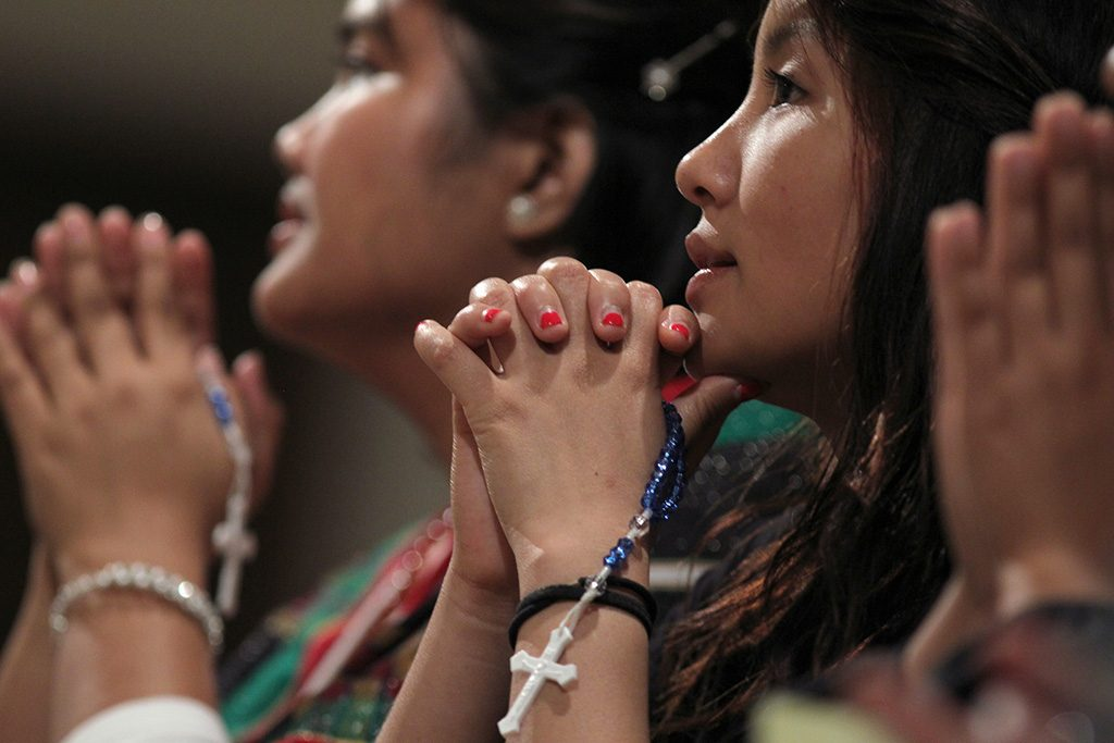 Hmong Catholics pray the rosary during a pilgrimage