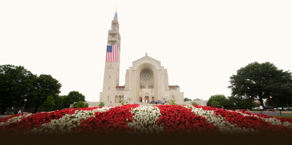 basilica front exterior with red and white flowers