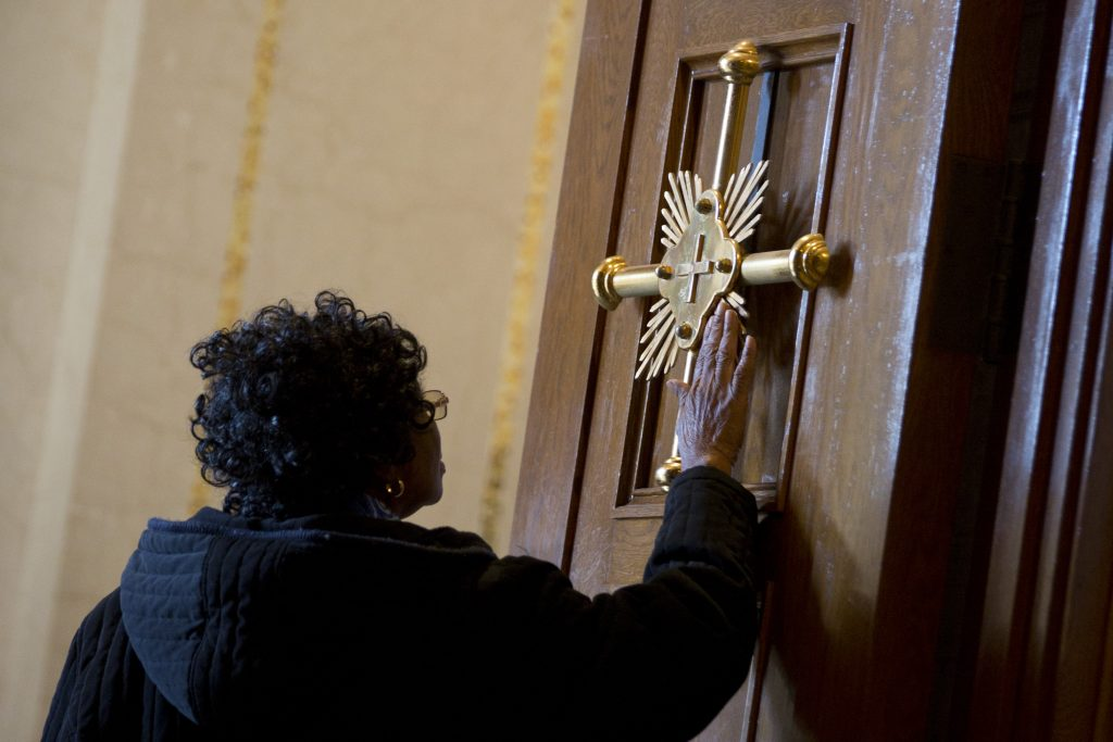 woman touches gold cross on door
