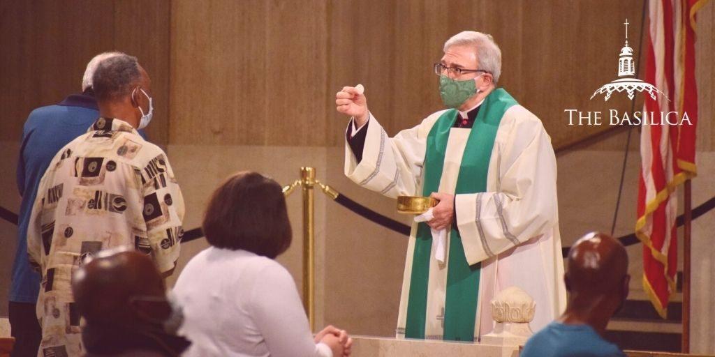 monsignor vito administers communion